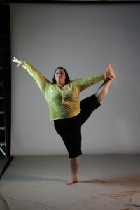 Ragen Chastain - Ragen is pictured in a dance pose against a white backdrop. She is caucasian, fat, with long dark wavy hair and a determined look on her face. She balances on her right foot, while she stretches her left foot high, up near her head, and holds it with her left hand. Her right hand is gracefully reaching up and away from her toward the right.