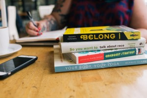 Business coaching for yoga studio owners: photograph shows a tabletop with 4 books, an iphone, coffee cup, and Amber's arms and chest in the background. She's writing in a journal.