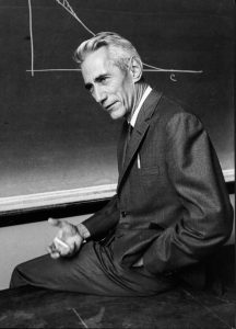 Photo of Claude Shannon sitting in front of blackboard