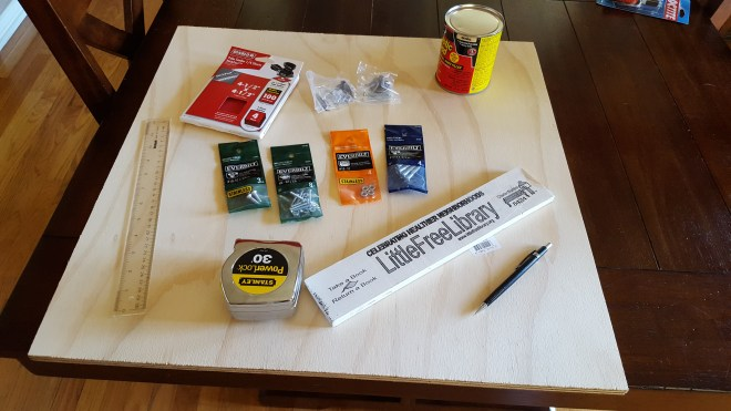 Photo of plywood, ruler, tape measure, screws, nuts, sandpaper, pencil, and Little Free Library placard.