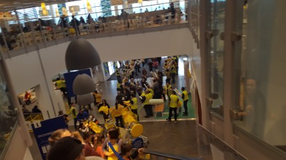 A view from the top of the escalator with employees cheering on incoming customers.