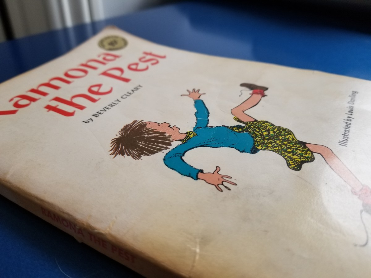 Aged and brown book cover of the 1968 edition of Ramona the Pest by Beverly Cleary viewed at an oblique angle on a blue desktop. There's a 95 cent scholastic price sticker on the upper right corner of the book. A cartoon-esque sketch of Ramon with her short-cropped hair brightly graces the cover.
