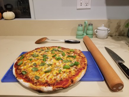 Homemade pizza: BBQ chicken with grilled onions, red peppers, fresh basil, mozerella, cheddar cheese, and Parmesan