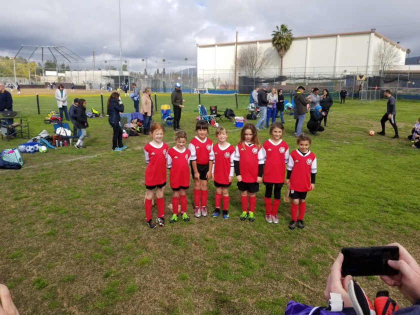 Seven 7 and 8 year olds in red soccer uniforms pose for a photo after the last game of the season.