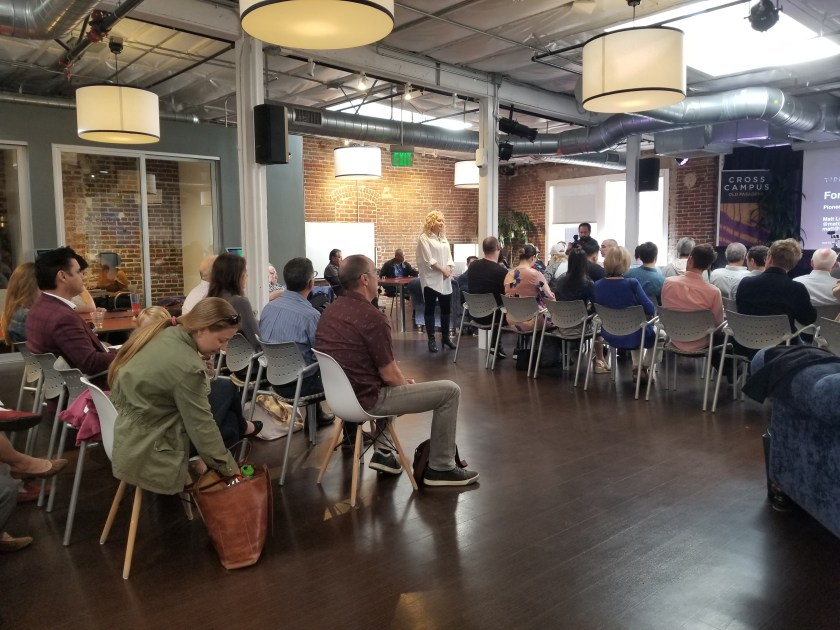 approximately 100 people in chairs in a modern coworking space rearranged to facilitate a speaker up on stage
