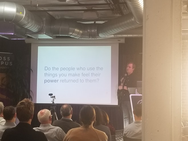 """Matt Lumpkin on stage with a slide displaying the text """"Do the people who use the things you make feel their power returned to them?"""""""