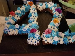 A cupcake display in the shape of the number 42 that is about 10 cupcakes tall. The frosting is in alternating white and blue with a few flowers, some blueberries and some baseball appliques