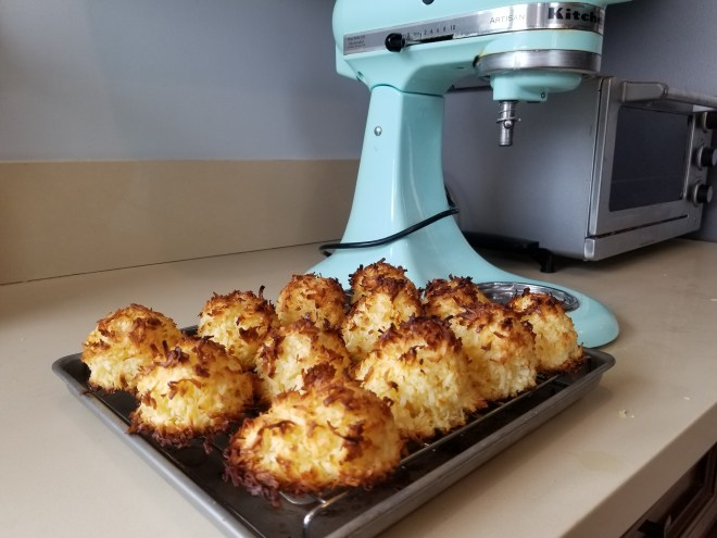 Well baked macaroons with browned edges on a cooling rack in the foreground and teal stand mixer in the background