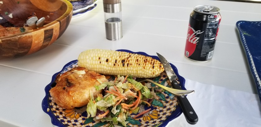 Grilled chicken, ear of corn, and tossed salad with can of coke zero