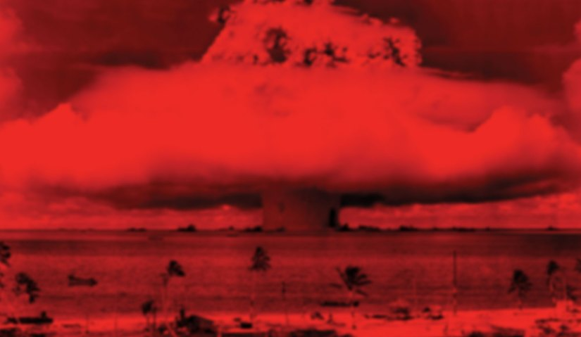 Image artwork from the cover of Ruined by Design featuring a red filtered view of the atomic mushroom cloud explosion on a small ocean island