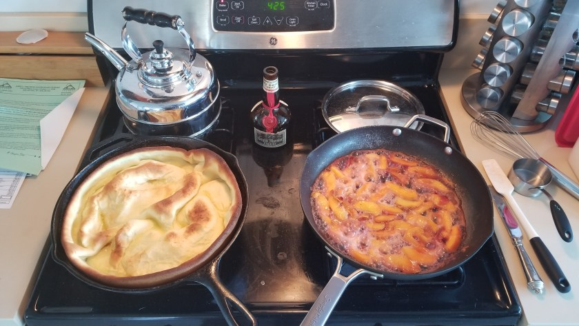 View of stovetop with Dutch baby in cast iron on the left, a pan with peaches bubbling in Grand Marnier on the right