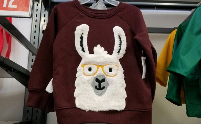 Brown shirt with a furry llama wearing gold framed glasses