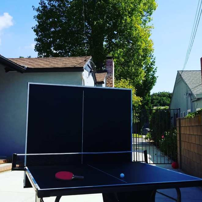 Ping pong table with half of it folded up as a backstop