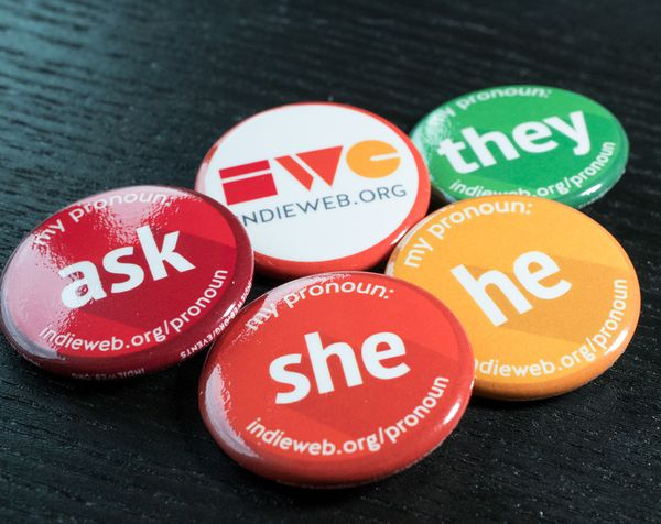 Multi-colored pronoun buttons for she (orange), he (yellow), they (green), and ask (red) as well as an IndieWebCamp button