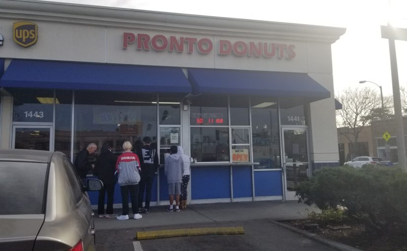A line of people in front of Pronto Donuts