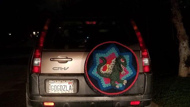 Honda CRV with crocheted tire cover featuring Godzilla