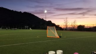 Bright orange and white lacrosse goal with the sun setting behind the mountain