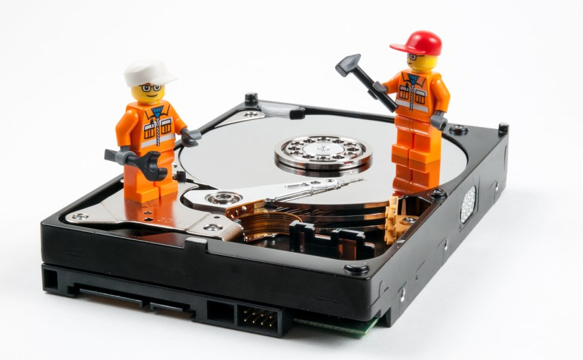 Two Lego figurines in workperson's costume standing on a computer hard drive with tools