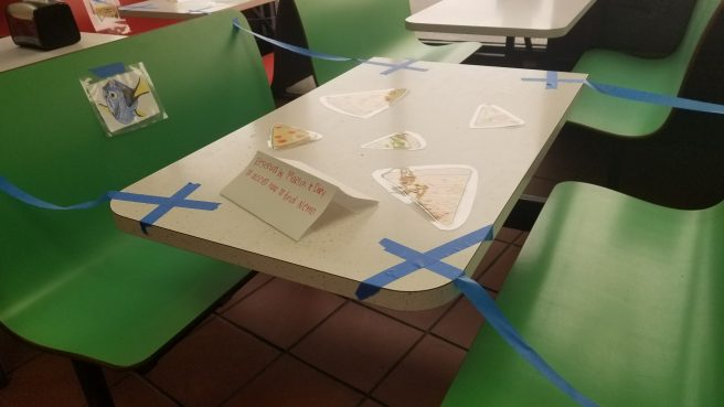 Green table/booth taped off with blue tape to force physical distancing within the restaurant