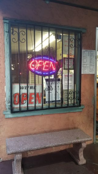 """A generic LED """"Open"""" sign behind black metal bars"""