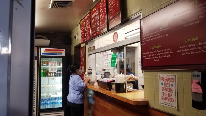 View into the small interior where a woman is placing an order. Only one customer at a time can fit in due to physical distancing for the coronavirus.