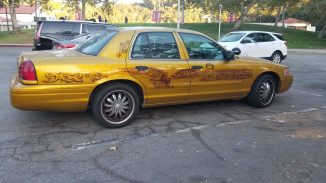 Goldish yellow Ford Crown Victoria with an airbrushed custom paint job featuring a large bald eagle on the rear passenger door and Jerry Orbach on the front passenger door.