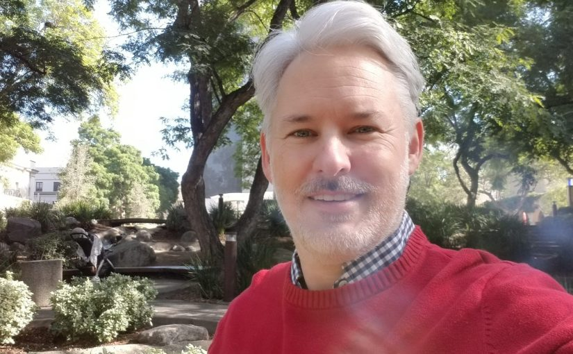 selfie of Chris Aldrich in red sweater with the Caltech Turtle Pond in background