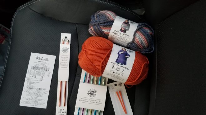 two balls of yarn and chrochet and knitting needles with receipt on black leather car seat