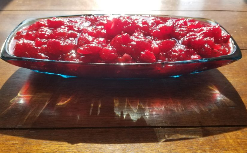 Blue glass dish full of cranberry sauce