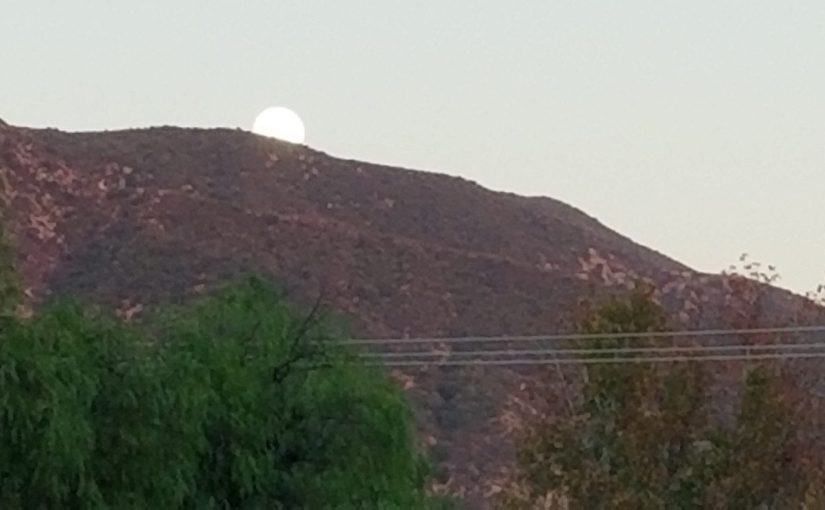 close up view of moon rising right at the mountains behind Eaton Canyon