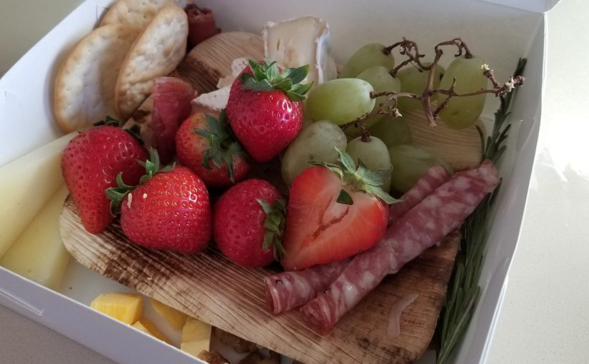 white cardboard box with a charcuterie board inside