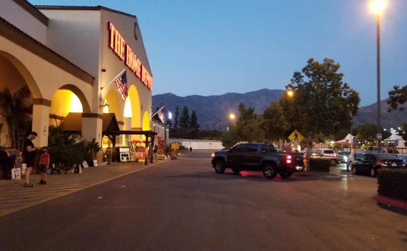 angle on front of Home Depot at dusk with Christmas Tree section on the right in the parking lot