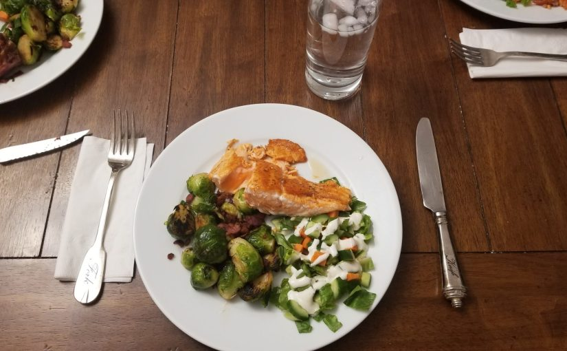 dining room table with plate of fried salmon, Brussels sprouts with bacon and small green salad with white dressing