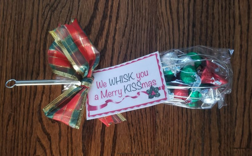 """A metal whisk filled with Hershey kisses and rapped in cellophane and a bow with a card that reads """"We WHISK you a merry KISSmas"""""""