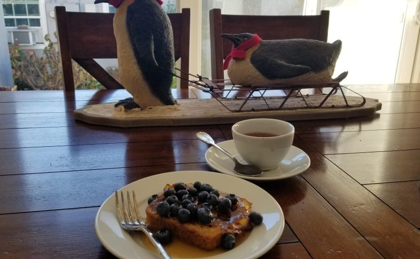 dining room table with penguin centerpiece and a plate with a slice of French toast, syrup, and blueberries with a teacup and saucer of tea