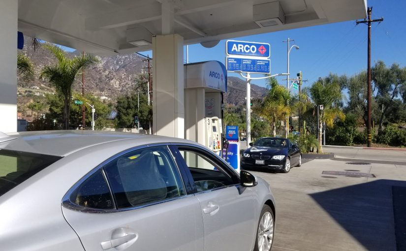 Grey Lexus under Arco awning looking at the Arco sign with the mountains nin the background