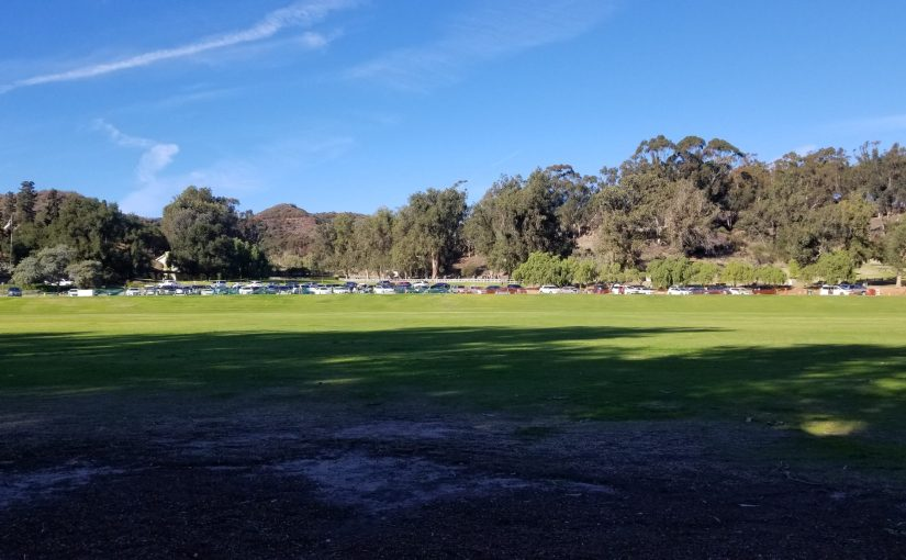 View across empty Will Rogers Park Polo fields looking up at trees and hill behind it