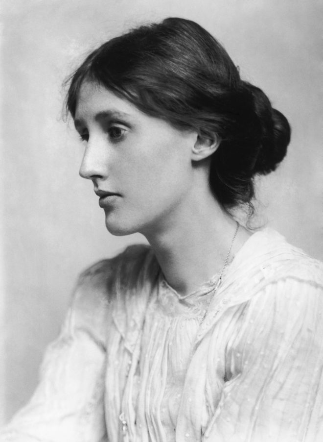 black and white photo of Virginia Woolf in profile wearing a white top and with her hair pulled back into a bun.
