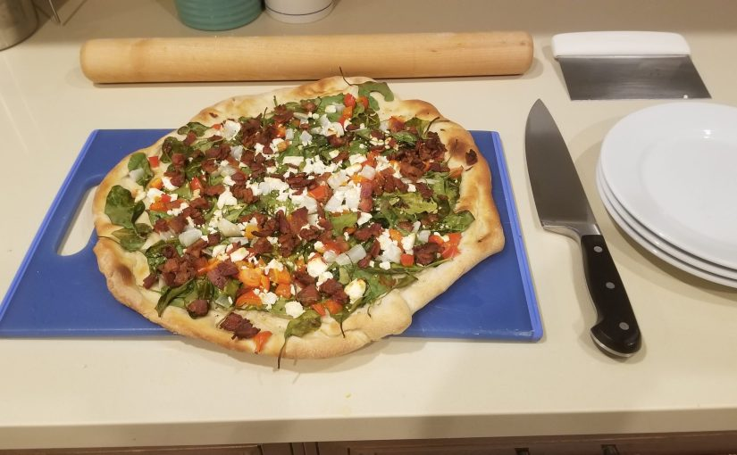rustic looking pizza on blue cutting board next to chef's knife and a rolling pin in the background