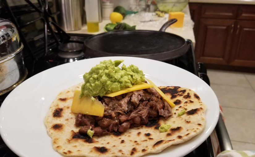 handmade flour tortilla with brown beans, pulled pork, cheddar cheese and avocado on a plate on the stove with tortialla making mise en place in the background