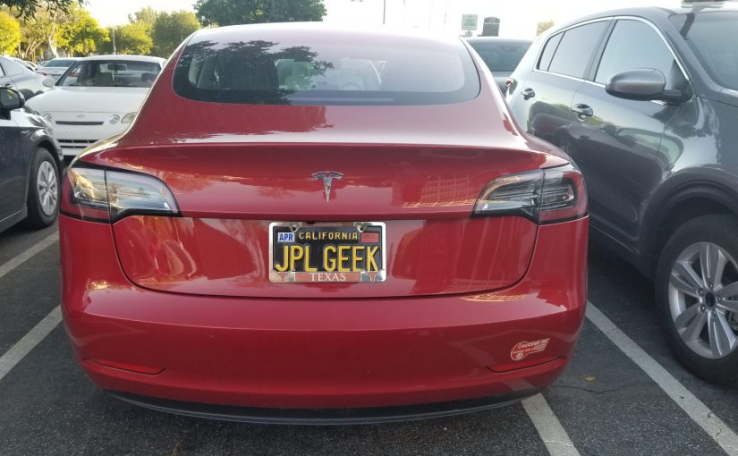 Red Tesla with black and yellow California plate reading JPL Geek