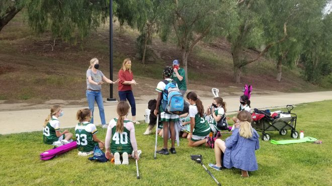 post-lacrosse huddle by coaches and players to review over the good things that happened in the game