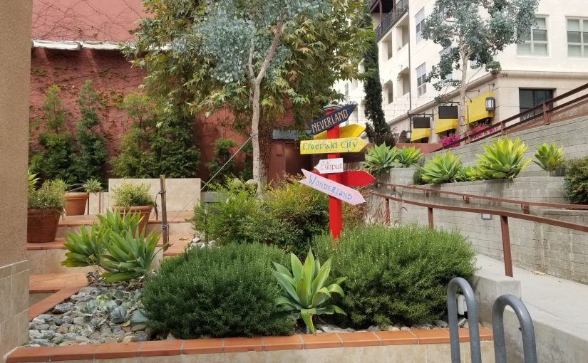 Signpost with directions of nearby fictional cities including Neverland, Emerald City, Liliput, and Wonderland amidst a garden of native southern California plants outside Vroman's bookstore