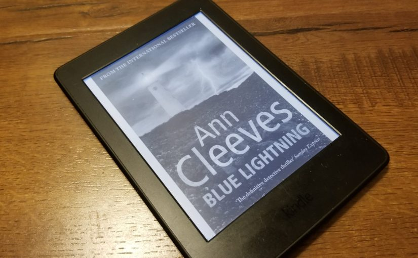 Kindle Paperwhite featuring the cover of Anne Cleeves' Blue Lightening with a lighthouse surrounded by a cloudy storm and a streak of lightening