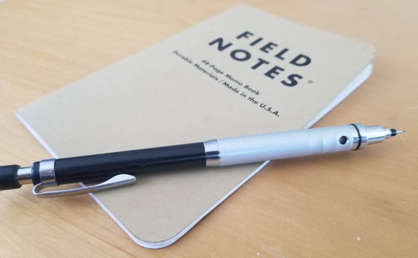 Field Notes 48 page small notebook on a wooden lapdesk with a mechanical pencil sitting on top of it.