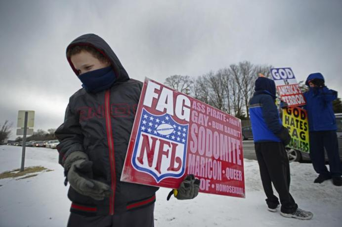 Luke Phelps-Roper, 11, holds a sign during the Westboro Baptist picket Saturday on Stadium Boulevard. There were many children participating in the picketing. MICHAEL CALI /The Maneater
