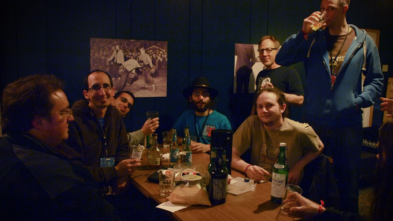 Whisky drinkers at 29c3 in Hamburg. The woman is behind the camera: Quinn Norton, of Boing Boing
