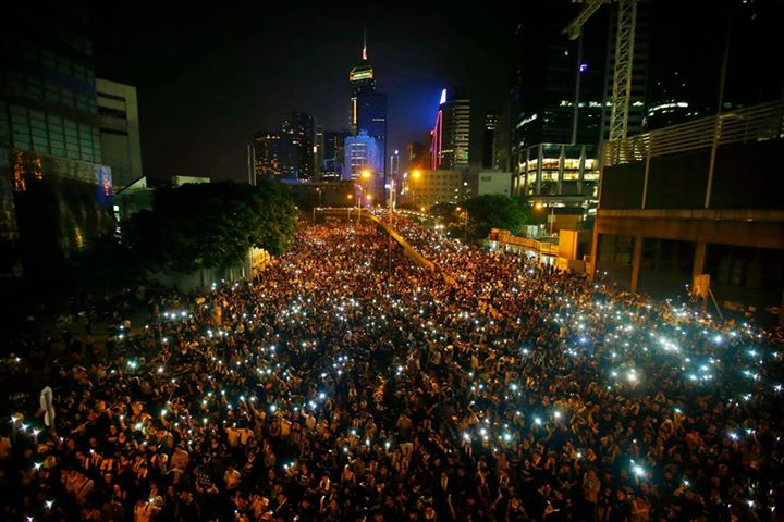 """Protesters block the main street to the financial Central district, outside the government headquarters, in Hong Kong, September 29, 2014. The banners read, """"I want a real general election"""" (C) and """"Embracing freedom in the storm"""" (R).  [REUTERS/Carlos Barria]"""