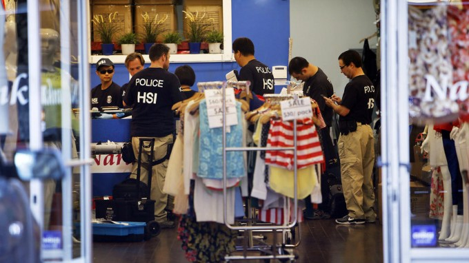 """Federal agents gather evidence from a business as they launched a series of raids in the downtown Los Angeles fashion district."" [Al Seib / Los Angeles Times]"