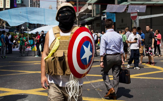 A protester of the Occupy Central movement carries a shield from the 'Captain America' comic book series as he stands on a main road at the Mong Kok shopping district in Hong Kong. [Reuters]